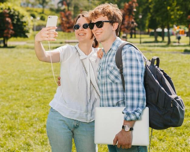 Junge paare, die selfie im park nehmen