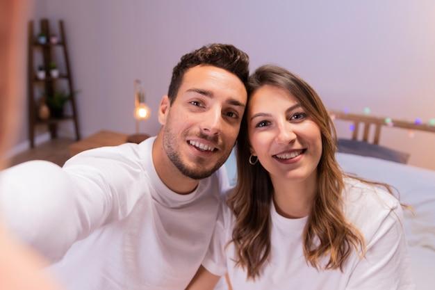Junge paare, die selfie im schlafzimmer nehmen