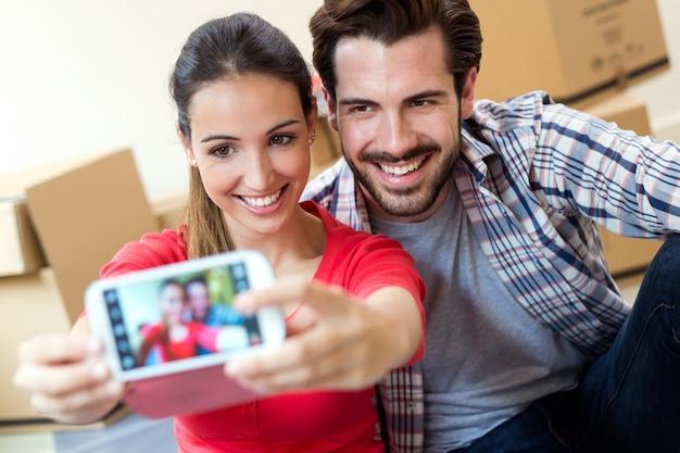 Junge paare, die selfies in ihrem neuen haus nehmen