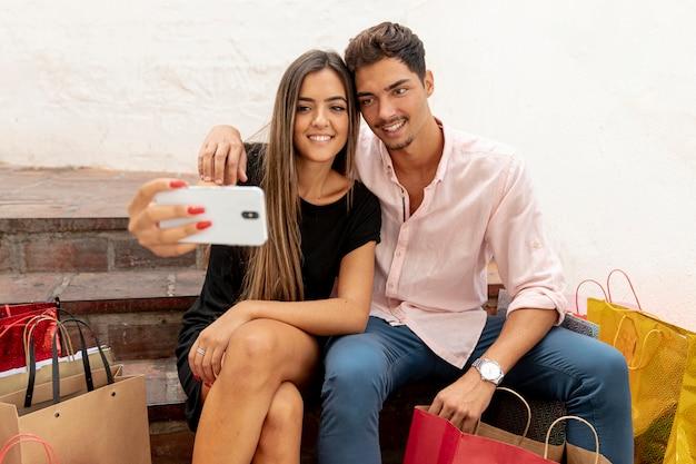 Junge paare, die selfies nahe bei einkaufstaschen nehmen