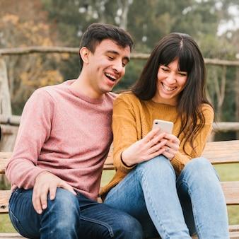 Junge paare, die smartphoneschirm betrachtend lachen
