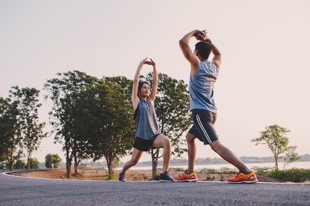 Junge paare, die übungen tun und vor lauf und körperlicher eignungsprüfung aufwärmen