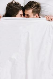 Junge paare, die unter weißer decke sich verstecken
