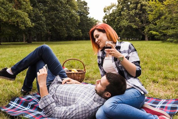 Junge paare, die video am handy am picknick aufpassen