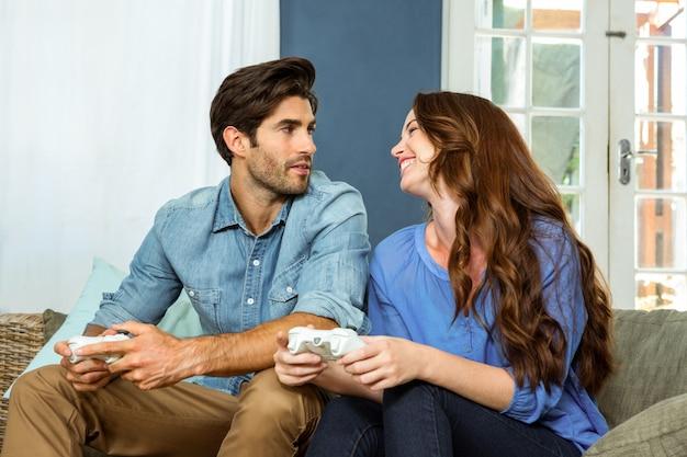 Junge paare, die videospiel beim sitzen auf sofa spielen