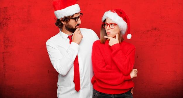 Junge paare, die weihnachtskonzept ausdrücken. paar und hintergrund in verschiedenen schichten