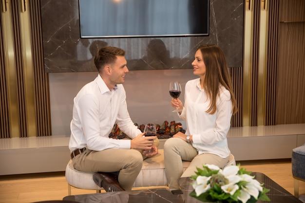 Junge paare, die zu hause einen romantischen abend mit einem glas rotwein im zeitgenössischen wohnzimmer haben