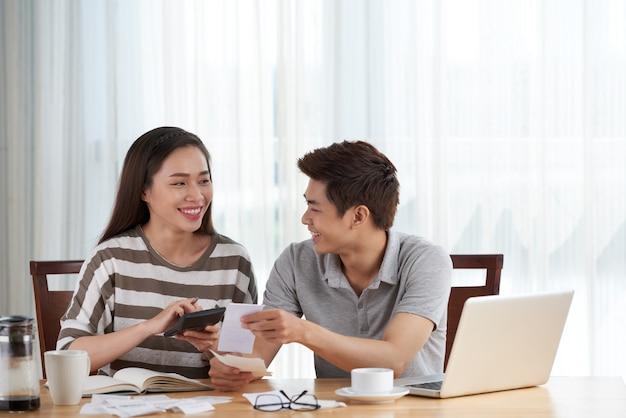 Junge paare, die zu hause familienbudget handhaben