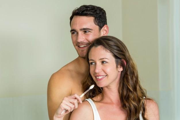Junge paare, die zu hause ihre zähne im badezimmer putzen