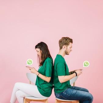 Junge paare, die zurück zu rückseite unter verwendung whatsapp auf smartphone sitzen
