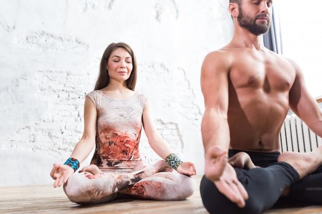 Junge paare, die zusammen, frau und mann sitzen rücken an rücken meditieren