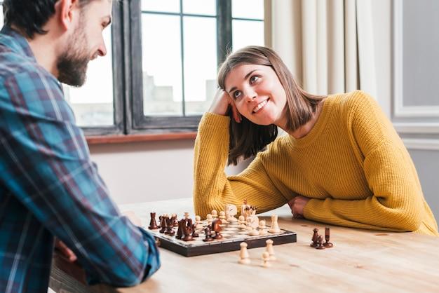 Junge paare, die zusammen sitzen, zu hause spielend das schach