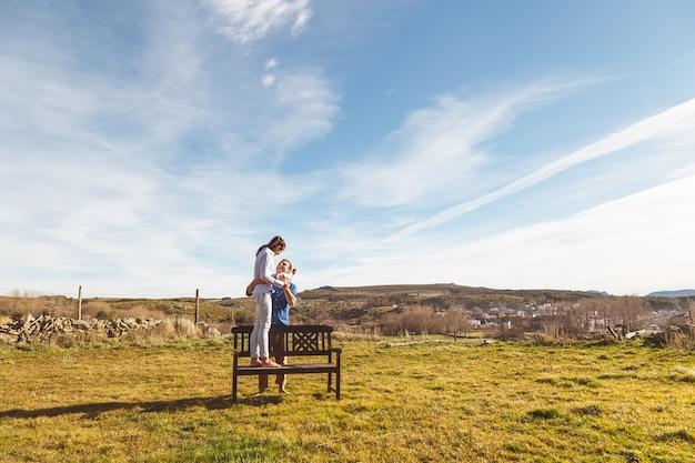 Junge paare, die zusammen zeit in der landschaft verbringen umarmen und genießen