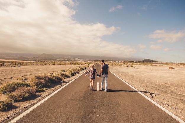 Junge paare gehen zusammen auf einer langen geraden straße mitten in einer wüste nirgendwo?