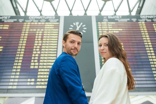 Junge paare im internationalen flughafen, der das fluginformationsbrett betrachtet