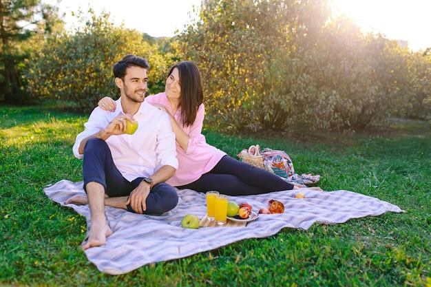 Junge paare im park, der draußen ein picknick hat