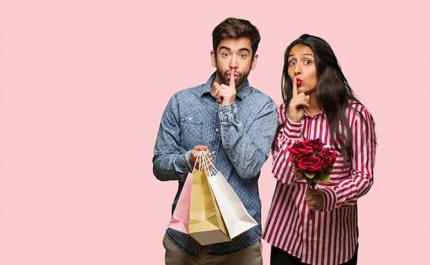 Junge paare im valentinsgrußtag, der ein geheimnis hält oder um ruhe bittet