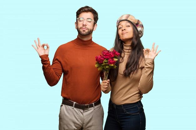 Junge paare im valentinsgrußtag, der yoga durchführt