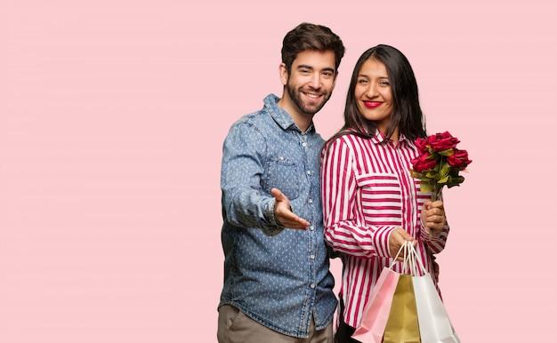 Junge paare im valentinsgrußtag heraus erreichen, um jemanden zu grüßen
