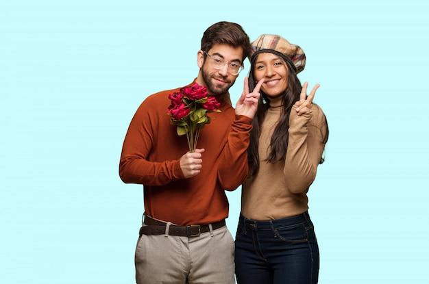 Junge paare im valentinsgrußtagespaß und glücklich, eine geste des sieges tuend