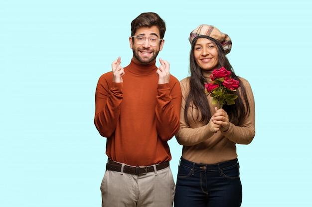 Junge paare in den valentinsgrußtageskreuzungsfingern für das glück haben