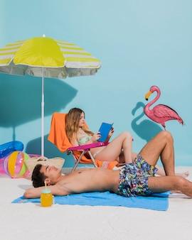 Junge paare in der badebekleidung, die auf strand sich entspannt