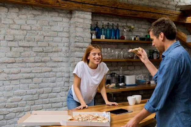 Junge paare in der liebe, die pizza im rustikalen haus isst