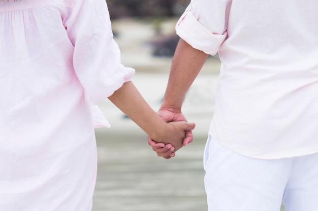 Junge paare in der liebe, die zusammen in das seehändchenhalten im süßen kleid der paare geht.