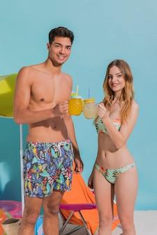 Junge paare in klirrenden cocktailgläsern der badebekleidung