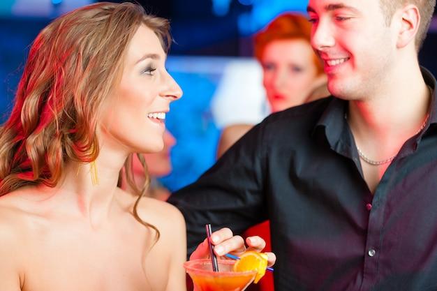 Junge paare in trinkenden cocktails der bar oder des vereins