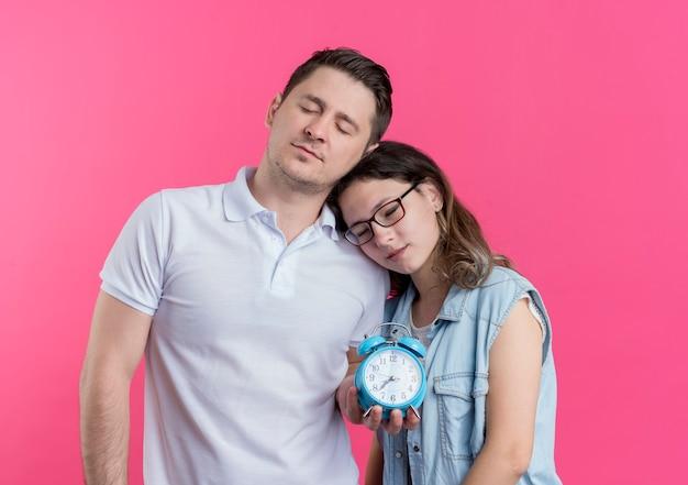 Junge paare mann und frau in freizeitkleidung zusammen halten wecker wollen mit geschlossenen augen über rosa schlafen