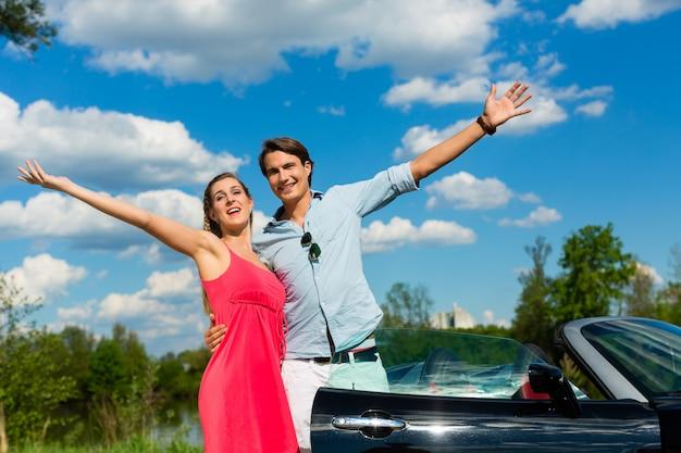 Junge paare mit cabriolet im sommer auf tagesreise