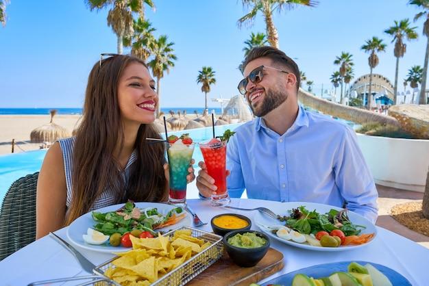 Junge paare mit cocktails im poolrestaurant