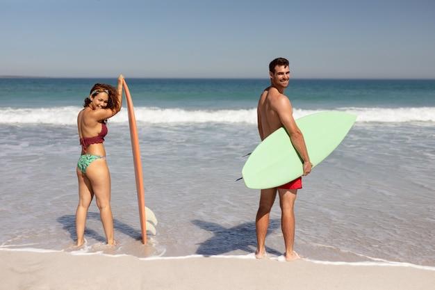 Junge paare mit dem surfbrett, das kamera auf strand im sonnenschein betrachtet