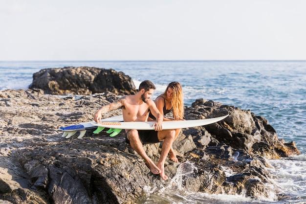 Junge paare mit den surfbrettern, die auf steinigem ufer sitzen
