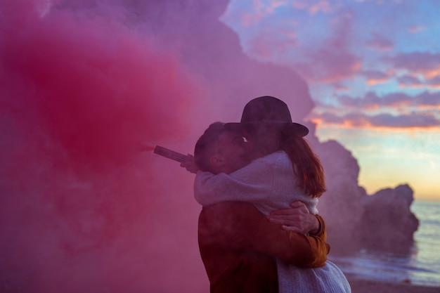 Junge paare mit der rauchbombe, die auf seeufer küsst