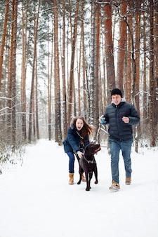 Junge paare mit einem hund, der spaß im winter hat