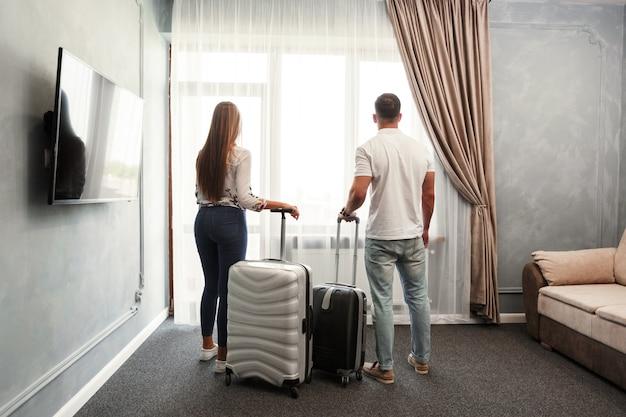 Junge paare reisen zusammen hotelzimmerfreizeit
