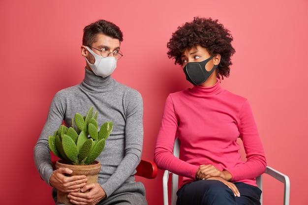 Junge paare schauen sich traurig an, tragen gesichtsmasken während der quarantäne zu hause pose auf stühlen vermeiden ansteckung und bleiben sicher tragen topfkaktus
