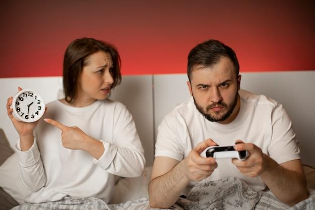 Junge paare streiten sich im schlafzimmer wegen spielsucht