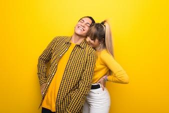 Junge Paare über dem vibrierenden gelben Hintergrund, der unter Rückenschmerzen leidet