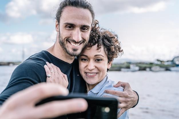 Junge paare umfasst durch die schulter, die ein selfie mit dem hafen und dem meer unscharf macht