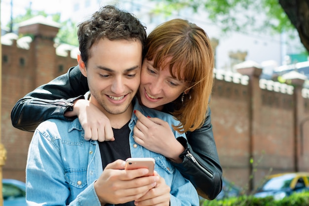 Junge paare unter verwendung der anwendung auf smartphone