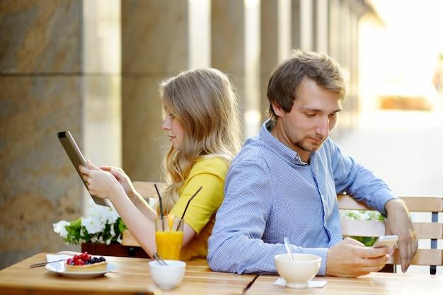 Junge paare unter verwendung des intelligenten telefon- und tabletten-pc im café im freien