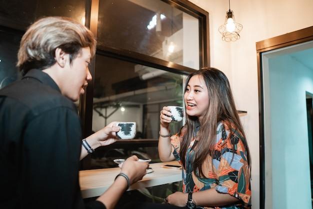 Junge paare unterhalten sich und genießen eine tasse kaffee, während sie in einem café sitzen