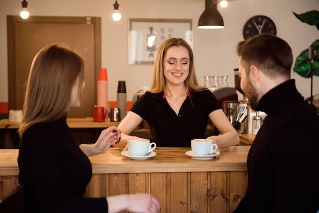 Junge paare von den kunden, die kaffee vom barista in der kaffeestube nehmen.