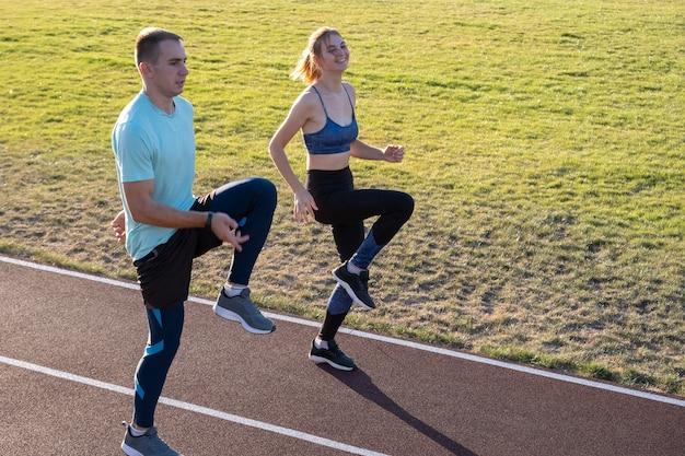 Junge paare von fitten sportlerjungen und -mädchen, die laufen, während übung auf roten spuren des öffentlichen stadions draußen tun.