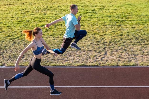 Junge paare von fitten sportlerjungen und -mädchen, die laufen, während übung auf roten spuren des öffentlichen stadions im freien tun.