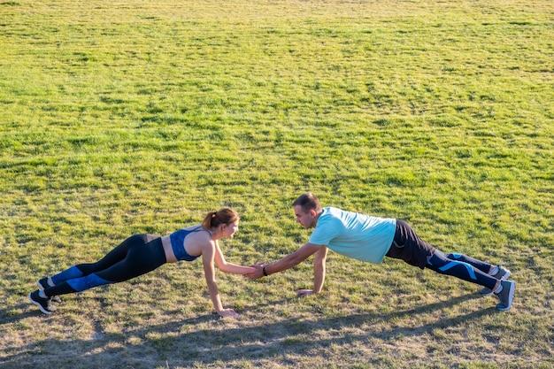 Junge paare von fitten sportlerjungen und -mädchen, die übung auf grünem gras des öffentlichen stadions im freien tun.