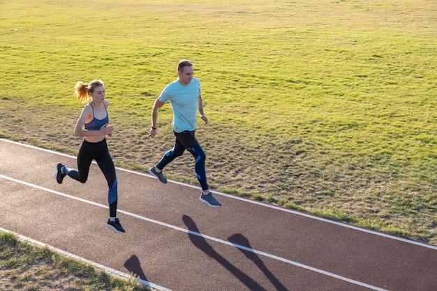 Junge paare von fitten sportlern jungen und mädchen laufen, während übung auf roten spuren des öffentlichen stadions im freien.